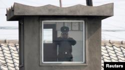 지난 4월 북한 접경도시 신의주의 국경 초소에서 북한 병사가 망원경으로 중국 쪽을 바라보고 있다. 압록강 너머 중국 단둥에서 촬영한 사진이다.