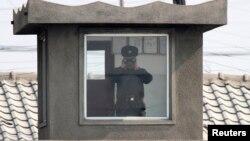 2014年4月7日一个朝鲜士兵在新义州附近通过望远镜观察鸭绿江对面的中国边境城市丹东