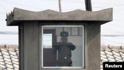 지난 4월 북한 접경도시 신의주의 국경 초소에서 북한 병사가 망원경으로 중국 쪽을 바라보고 있다. 압록강 너머 중국 단둥에서 촬영한 사진이다. (자료사진)
