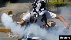6일 베네수엘라 카라카스에서 대규모 반정부 시위가 벌어진 가운데, 한 참가자가 경찰이 발사한 최루탄을 다시 경찰을 향해 던지고 있다.