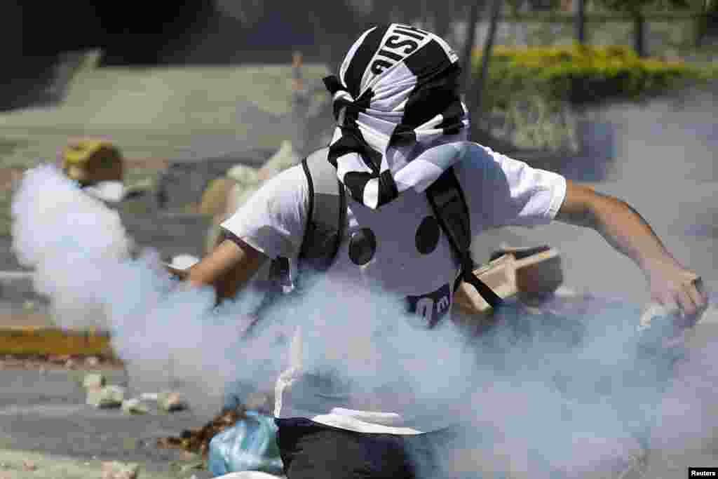 An anti-government protester throws a gas canister back at police during riots in Caracas, April 6, 2014. Protesters have been on the streets since early February calling for President Nicolas Maduro's resignation and complaining about a litany of problems from rampant crime to food shortages.