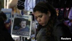 """ស្រ្តីម្នាក់ដើរកាត់កាសែតមួយច្បាប់ដែលបង្ហាញរូបមេខ្លោងជួញដូរគ្រឿឿងញៀន Joaquin """"Chapo"""" Guzman លើទំព័រមុខក្នុង Culiacan ប្រទេសម៉ិកស៊ិក កាលពីថ្ងៃទី៦ មករា ឆ្នាំ២០១៦"""