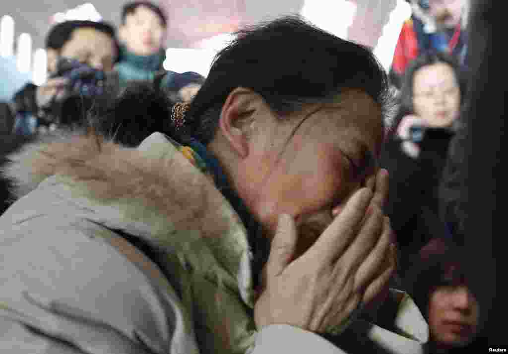 A relative of a passenger onboard Malaysia Airlines flight MH370 cries, surrounded by journalists, at the Beijing Capital International Airport in Beijing, China.