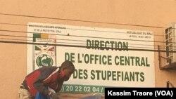 Un homme décharge la drogue d'un camion devent l'Office central des stupéfiants du Mali à Dio, 28 mars 2018. (VOA/Kassim Traore)