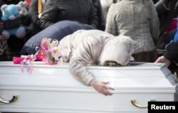 在为一名克麦罗沃商城火灾受害者举行的葬礼期间,一位女士在墓地抚棺痛苦。(2018年3月28日)