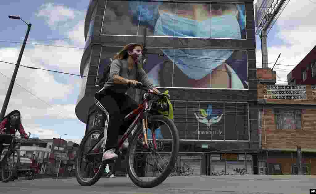 Women wearing protective face masks pedal past on bicycles in Bogota, Colombia, Thursday, July 23, 2020,