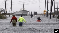 People wade and paddle down a flooded street as Hurricane Sandy approaches, Monday, Oct. 29, 2012, in Lindenhurst, N.Y