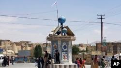 Bendera Taliban berkibar di sebuah alun-alun di kota Ghazni, Afghanistan, setelah pertempuran antara Taliban dan pasukan keamanan Afghanistan Kamis, 12 Agustus 2021. (AP Photo/Gulabuddin Amiri)