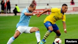Manchester City's Pablo Zabaleta (L) fights for the ball with Arsenal's Alex Oxlade-Chamberlain during the two English Premier League teams' friendly soccer match at the Helsinki Olympic Stadium in Finland, August 10, 2013.