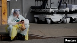 A healthcare worker sits on the curb as he uses a vaping device while taking a break outside.