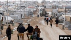 Syrian refugees travel on the main street of Al Zaatari refugee camp in the Jordanian city of Mafraq, near the border with Syria, Jan. 15, 2015.