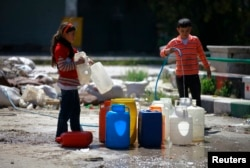 FILE - Children fill containers with water during a water shortage in the old city of Aleppo, Apr. 6, 2014.