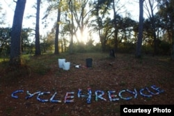 "Yana and Slav spell out ""Cycle4Recycle"" with cans they found in a park"