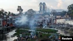 Víctimas del terremoto de Nepal son cremados a la orilla de un río en Karmandú, la capital.