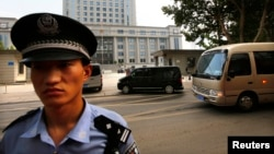 A minivan believed to be carrying disgraced Chinese politician Bo Xilai (C) arrives at the Jinan Intermediate People's Court ahead of Bo's fourth-day trial in Jinan, Shandong province Aug. 25, 2013.