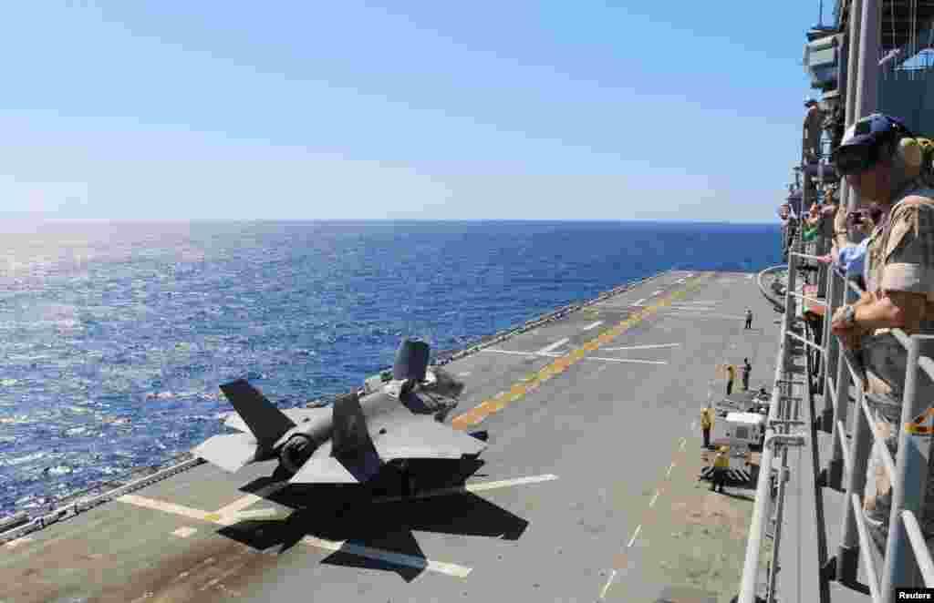 """在美国北卡罗来纳海岸,黄蜂号两栖攻击舰(The amphibious assault ship USS Wasp)上,一架F-35B战斗机准备在测试期间起飞(2015年5月26日)。2018年9月下旬,这艘军舰在东中国海(中国称东海)航行。本月早些时候台风""""山竹""""之后,该军舰抵达关岛和北马里亚纳群岛进行救灾。"""