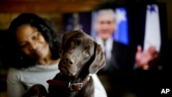 """Alicia Barnett sits with her Chocolate Labrador Retriever named """"Mueller"""" in their Kansas City, Kan., home on March 11, 2019."""
