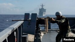 FILE - The Philippine Navy is upgrading its fleet amid growing maritime disputes. Here, one of its troops fires a .50-caliber machine gun during a bilateral maritime exercise between the Philippine Navy and U.S. Navy in the South China Sea, June 29, 2014.