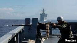 在菲美海軍在南中國海的海上演習中,一名菲律賓海軍士兵在軍艦上射擊,2014年6月29日(資料照片)
