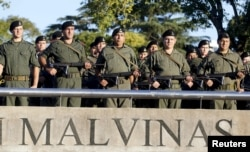 FILE - Officers pay tribute to the Argentine servicemen who died in the1982 Falklands War between Britain and Argentina on the 33rd anniversary of the war over the island chain in Rosario, Argentina, April 2, 2015.
