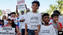 Hector Rivera, 8, Mario Jordan Micael, 3, and Ramon Montes, 5, participate in a rally in West Palm Beach, Fla., Sept. 22, 2018, marking the one-year anniversary of Hurricane Maria's devastation of Puerto Rico.