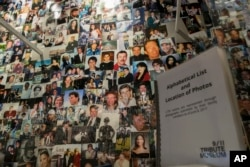 FILE - Photographs of some of those who died during the terrorist attacks on the World Trade Center, the Pentagon, and Shanksville, Pennsylvania, are on display at the 9/11 Tribute Museum in New York, June 8, 2017.