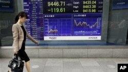 日本女士走过股市行情屏幕
