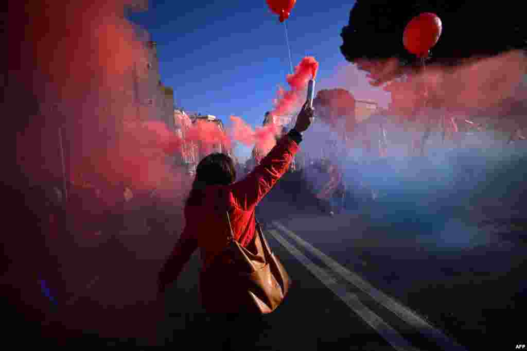 A demonstrator holds flares during a general strike in Rome, called by several trade unions. Unions are protesting against Italian Prime Minister Matteo Renzi's emblematic Jobs Act legislation which aims to shake up the labor market by making it easier for companies to hire and fire.