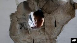 30일 가자지구 북부 유엔 학교에 포격이 있은 후, 한 소년이 구멍이 뚫린 학교 건물 사이로 얼굴을 들이밀고 있다.