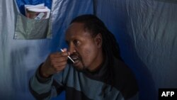 FILE: Forty-five year-old Oscar Tyumre uses an HIV self-testing kit, administered by students from the University of the Witwatersrand in Hillbrow, Johannesburg, on March 19, 2018. Self-testing kits and vending machines distributing prescription drugs are two ways that