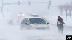 Seorang pria menelepon untuk menunggu bantuan setelah mobilnya terjebak dalam badai salju di kota Lawrence, Kansas hari Minggu (24/11).