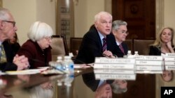 FILE - Federal Reserve Board member Daniel Tarullo, center, accompanied by Chair Janet Yellen (2nd left) Vice Chair Stanley Fischer (left), Jerome Powell, (2nd right) and Lael Brainard (right) during an open board meeting in Washington, Dec. 15, 2016.