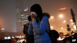 8일 짙은 스모그로 덮인 베이징 거리에서 시민들이 마스크로 입을 막고 있다.