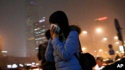 Una mujer se cubre la cara con una máscara mientras se dirige a una estación del tren subterráneo en Beijing, el martes, 8 de diciembre de 2015.