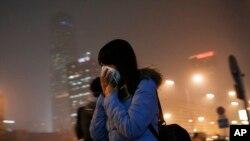 Phụ nữ che mặt trong lúc chạy vội đến nhà ga tàu điện ngầm ở Bắc Kinh, ngày 8/12/2015.