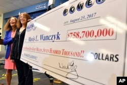 Mavis Wanczyk, of Chicopee, Mass., stands by a poster of her winnings during a news conference where she claimed the $758.7 million Powerball prize at Massachusetts State Lottery headquarters, Aug. 24, 2017, in Braintree, Mass. At left is state Treasurer Deb Goldberg.