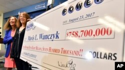 Mavis Wanczyk, of Chicopee, Mass., stands by a poster of her winnings during a news conference where she claimed the $758.7 million Powerball prize at Massachusetts State Lottery headquarters, Aug. 24, 2017, in Braintree, Mass. At left is state Treasurer