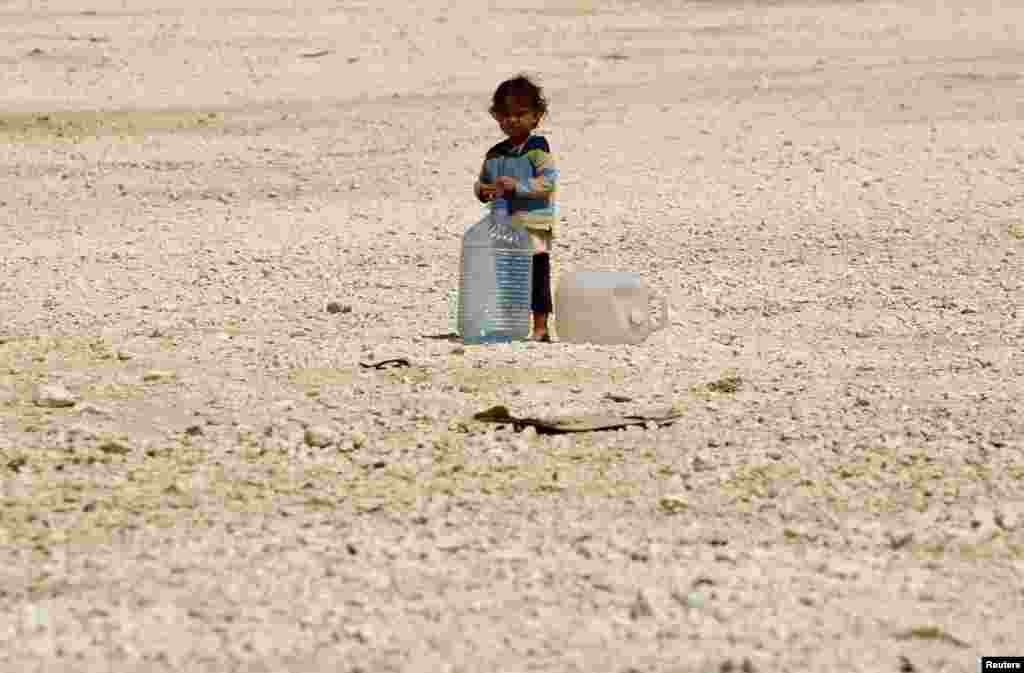 A young Syrian refugee stands beside water containers at Al-Zaatri refugee camp in the Jordanian city of Mafraq, near the border with Syria, Sept. 1, 2013.