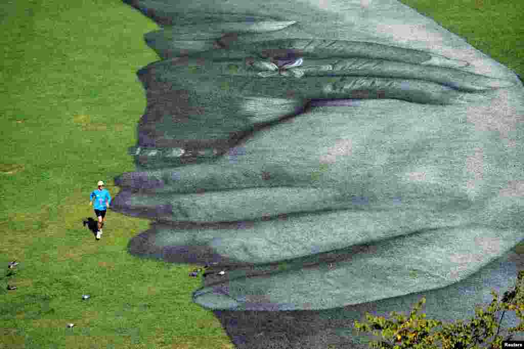 "A man jogs next to an artwork by French street artist Saype, called ""Beyond Walls"", a spray paint series of interlocked hands, painted across the grass in front of the Palatine Gate, as part of a project creating a spray-painted ""human chain"" across the world to encourage humanity and equality, in Turin, Italy, Sept. 30, 2020."