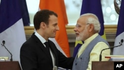 Perdana Menteri India Narendra Modi (kanan) berbincang dengan Presiden Perancis Emmanuel Macron seusai penandatangan kerjasama kedua negara di New Delhi, India, 10 Maret 2018.