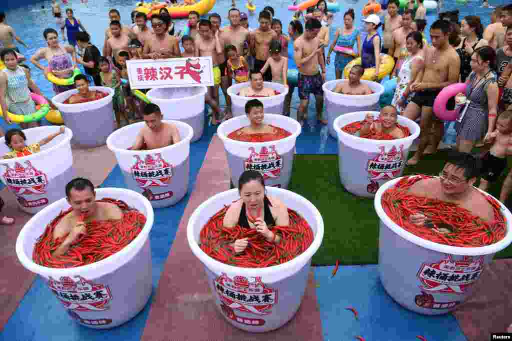 Participants take a bath in barrels filled with chili peppers during the Spicy Barrel Challenge contest inside a water park in Chongqing, China, July 7, 2018.