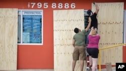 5일 푸에르토리코 토아바하에서 초강력 허리케인 '어마' 상륙을 앞두고 주민들이 상점 창문을 나무판자로 가리고 있다.