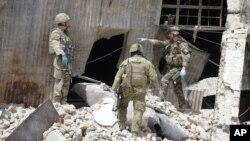 Soldados de la OTAN investigan la escena del ataque talibán de este miércoles, anunciado como respueta a la visita del presidente Barack Obama.