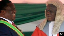 FILE: Zimbabwean President Emmerson Mnangagwa,left, is congratulated by Chief Justice Luke Malaba after taking his oath during his inauguration ceremony at the National Sports Stadium in Harare, Sunday, Aug. 26, 2018. T