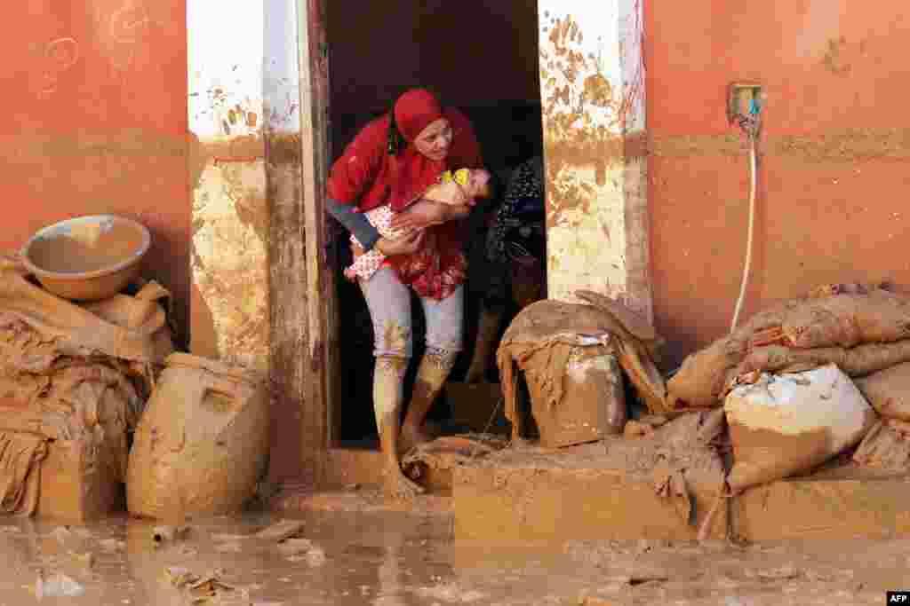 Seorang perempuan Mesirmenggendong bayinya di Ras Gharib, dekat Teluk Suez setelah banjir dan hujan melanda sebagian kawasan di sana.