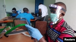 FILE - Workers prepare face shields from recycled plastics at the Zaidi Recyclers workshop as a measure to stop the spread of coronavirus disease (COVID-19) in Dar es Salaam, Tanzania, May 27, 2020.