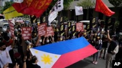 Protesters shout slogans as they hold a Philippine flag during a rally in front of the Chinese Consulate in Makati city, Philippines on Monday, July 12, 2021. The demonstration was held to commemorate the 5th anniversary of the Arbitral Ruling in…