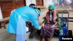 Volunteer checks the blood oxygen level of a coronavirus disease (COVID-19) patient in the town of Kale, Sagaing Region, Myanmar, July 5, 2021.