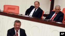 Prime Minister Binali Yildirim, rear right, smiles as he listens to opposition lawmaker Engin Altay before a parliamentary vote in Ankara, Turkey, Sept. 23, 2017. The Turkish parliament renewed a bill allowing the military to intervene in Iraq and Syria if faced with national security threats — a move seen as a final warning to Iraqi Kurds to call off their Monday independence referendum.