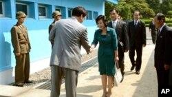 Bà Kim Sung-hye, giới chức cao cấp thuộc Ủy ban Thống nhất trong Hòa bình Bắc Triều Tiên bắt tay một sĩ quan Nam Triều Tiên trước khi bước qua lằn ranh quân sự tại làng Bản Môn Điếm, ngày 9/6/2013.